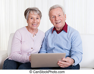 Senior Couple Looking At Laptop Computer - Senior Couple...