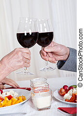 Close-up Of Hands Toasting Wine Glasses In Restaurant