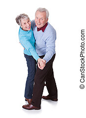Portrait Of Senior Couple Dancing On White Background