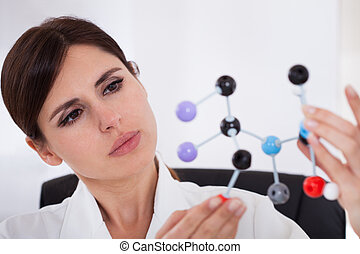 Scientist Looking At Dna Molecular Structure - Female...