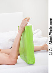 Woman Holding Shoppingbag With Leg - Close-up Of Womans Leg...
