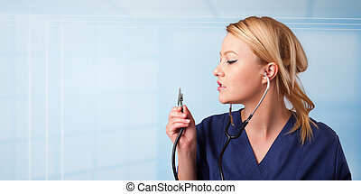 Pretty young nurse in hospital listening to empty copy space...