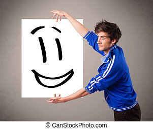 Young boy holding smiley face drawing - Handsome young boy...