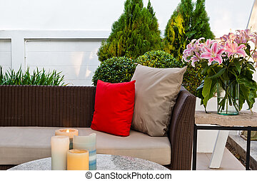 Outdoor patio seating area with nice Rattan sofa at sunset