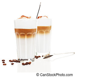 two glasses latte macchiato with coffee beans and chocolate powder on white background