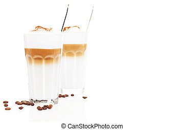 latte macchiato in front of another latte macchiato with coffee beans and spoons inside on white background