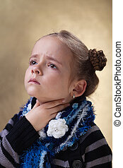 Little girl with sore throat in flu season touching her neck
