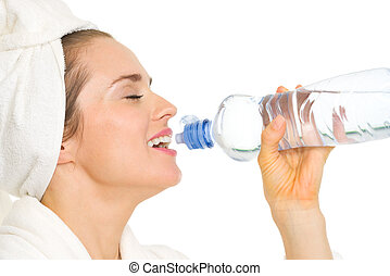 Young woman in bathrobe drinking from bottle with water