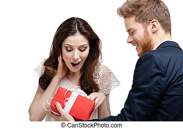 Young man amazes his pretty girlfriend with present wrapped...