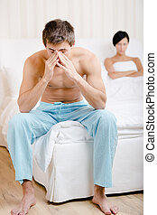 Young couple argues in bed-room