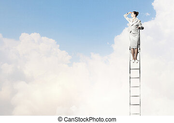 Businesswoman standing on ladder looking into distance...