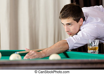 Male playing billiard at gambling house