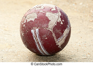 Old worn soccer ball lying on the g