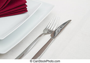 Place setting with white plates and red folded napkin