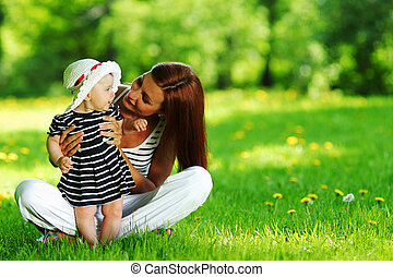 Mother and daughter on the green grass - Happy mother and...