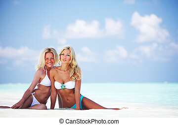 Two girls sitting on the ocean coast