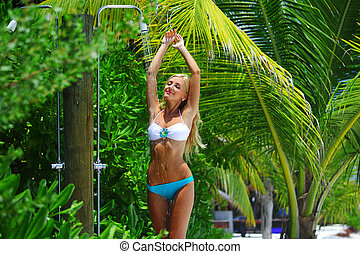 woman in tropical shower palms around