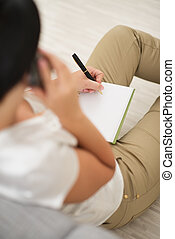 Young woman talking cell phone and writing in notepad. rear view