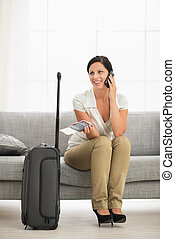 Happy young woman in living room with travel bag talking...