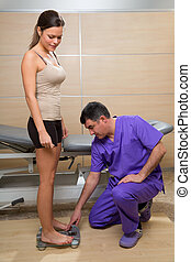 Doctor checking weight scale measure of woman patient in...