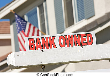 Bank Owned Real Estate Sign and House with American Flag in...
