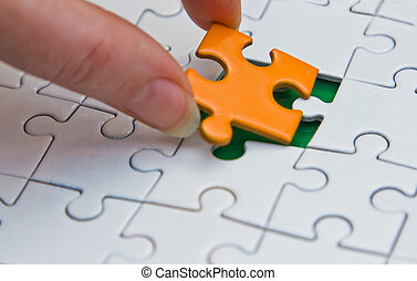 Hands placing piece of a Puzzle