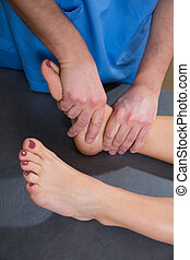 Ankle joint mobilization therapy of doctor man to woman -...