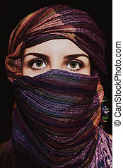 Portrait of beautiful green-eyed woman in hijab on black...