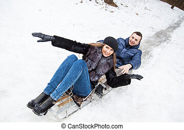 Young couple having fun riding on sledge