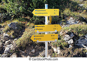 A signpost in the Allgaeu Alps - A yellow signpost with many...