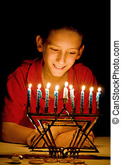 The Menorahs Glow - Little boy gazing on a lighted menorah,...