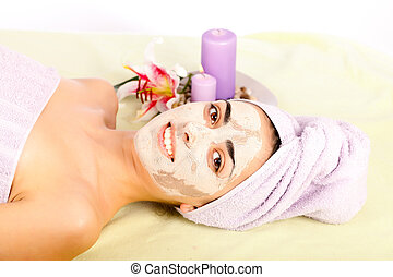 Beauty Treatment - Lying beautiful woman at spa with clay...