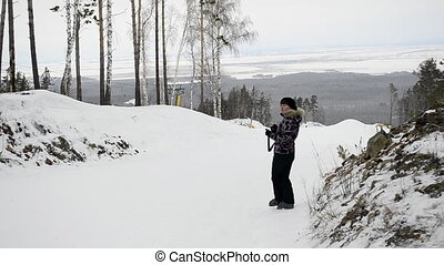 Young woman photographing skiers