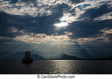 Sailing ship crossing the sea in front of mountain horizon under the cloudy sky.  Sun rays