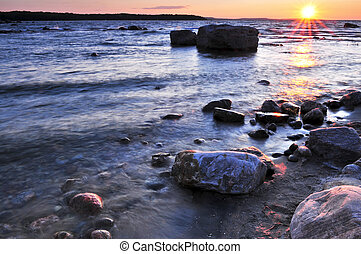 Sunset over water - Sunset at the rocky shore of Georgian...