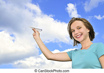 Young girl holding paper airplane - Young teenage girl...