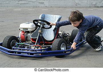 A boy pushes his racing car - A caucasian child pushes his...