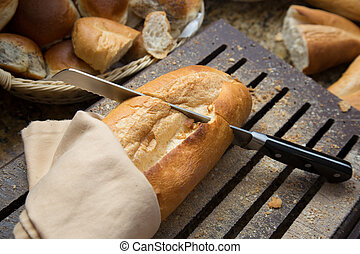 Man's hand cutting bread on a wooden board with a knife