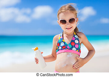 Sun protection - Adorable little girl at tropical beach...