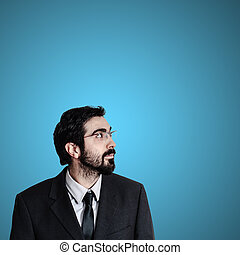 bearded business man looking up on blue background