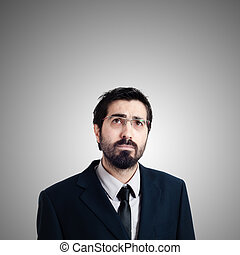 bearded business man looking up on gray background