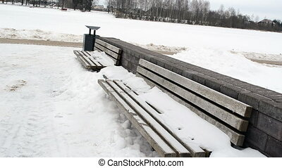 bench snow woman park - wooden benches covered with snow and...