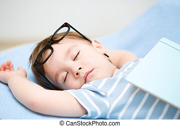 Cute little boy is sleeping while wearing glasses and put...