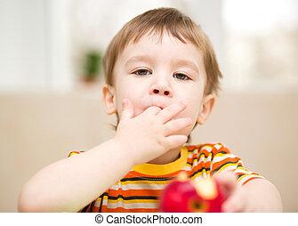 Little boy is eating apple