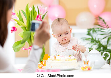 Mother making photos of daughter with birthday cake