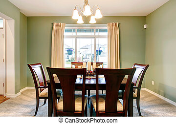 Green dining room interior with classic brown furniture.