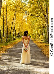 The bride with bouquet in the autumn forest