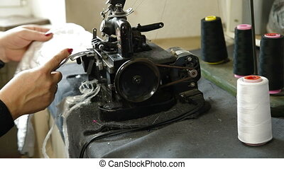 Overlock sewing machine - Tailor working at the overlock...