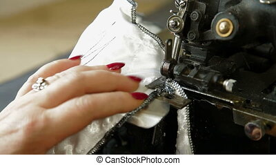 Overlock sewing machine - Women's hands are working at the...