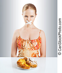 diet concept woman mouth sealed with duct tape with buns -...
